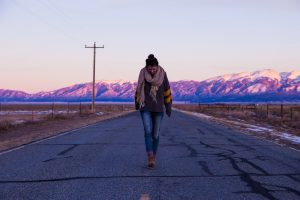 How can you overcome limiting beliefs? (Photo of woman walking along road, looking down, by Pete Johnson on StockSnap)